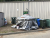 Existing conditions of the Earth Tub: covered by a gray tarp and weighed down by bricks and some other objects